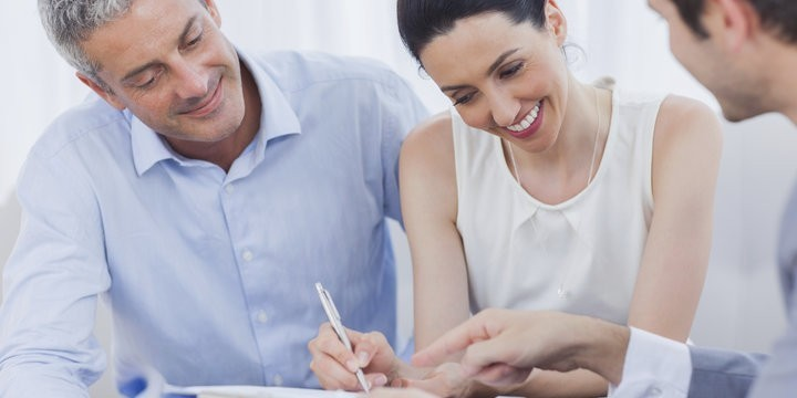 Smiling woman sign on a contrat with her partnership on sofa at office